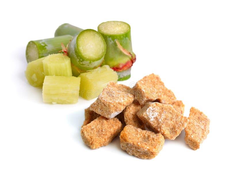 Canna da zucchero con zucchero bruno Isolato su priorità bassa bianca immagine stock libera da diritti