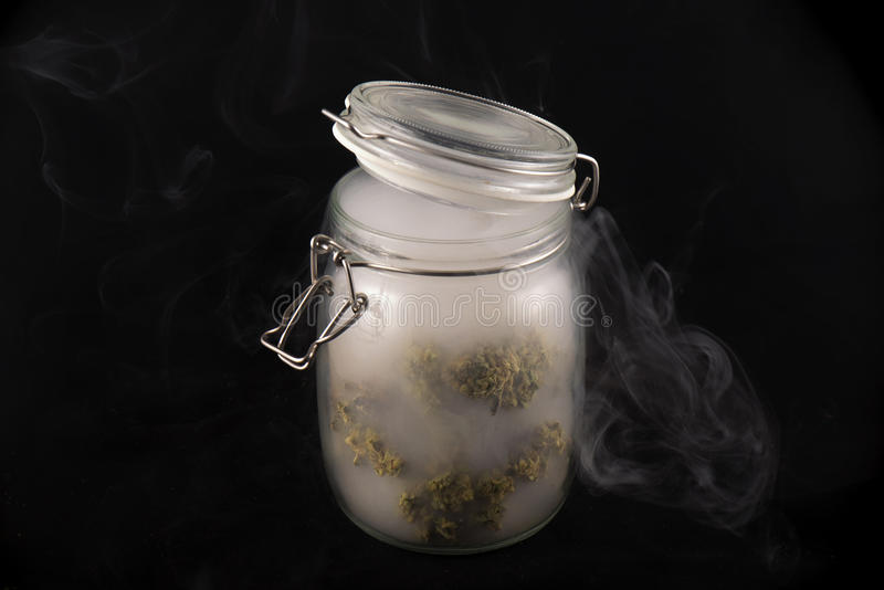 Cannabis buds maui skunk strain on a glass jar with smoke isol. Detail of cannabis buds maui skunk strain on a glass jar with smoke isolated on black background stock photography