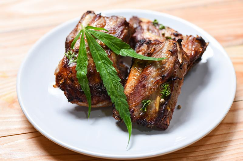 Cannabis food with bbq pork ribs grilled with herbs spices served on white plate - Roasted barbecue pork spare rib and marijuana stock images