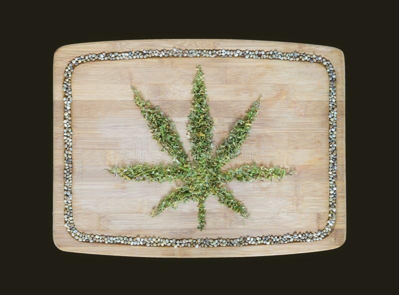 Cannabissymbol som göras av torkade hampasidor på en träbambuboa royaltyfri fotografi