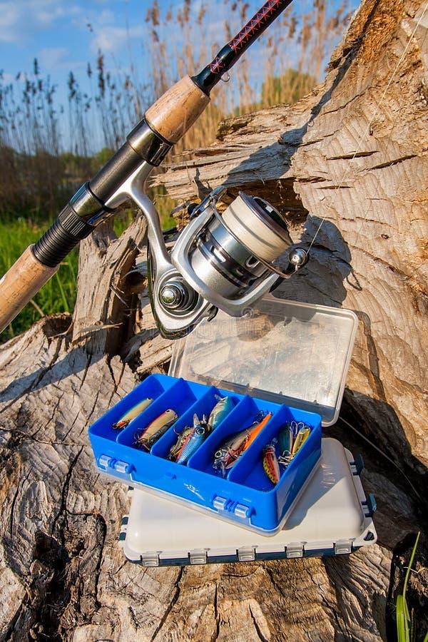 Canne à pêche avec la bobine et divers genre d'amorces sur le b naturel photos libres de droits
