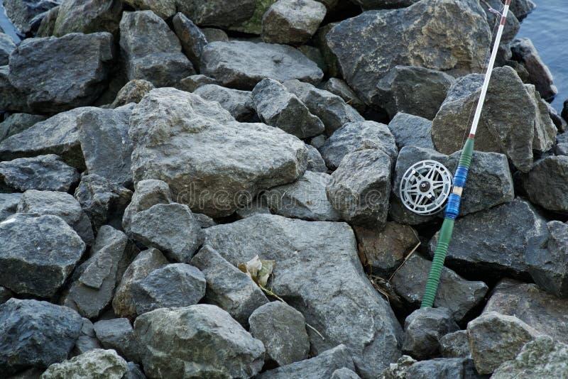 Canne à pêche et bobine de mouche sur la berge en pierre Scène de pêche sur les banques photos stock