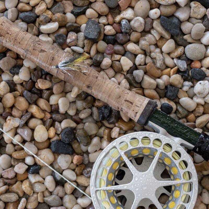 Canne à pêche et bobine de mouche sur le fond humide de caillou photos libres de droits