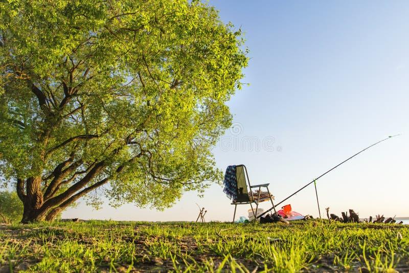 Canne à pêche et pêche de la chaise sous le grand arbre vert sur le beau rivage du lac ou de la rivière la soirée chaude d'été Pê photos stock
