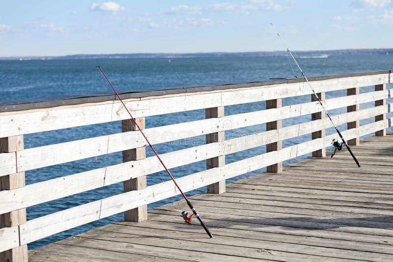 Canne da pesca allineate lungo un pilastro fotografia stock