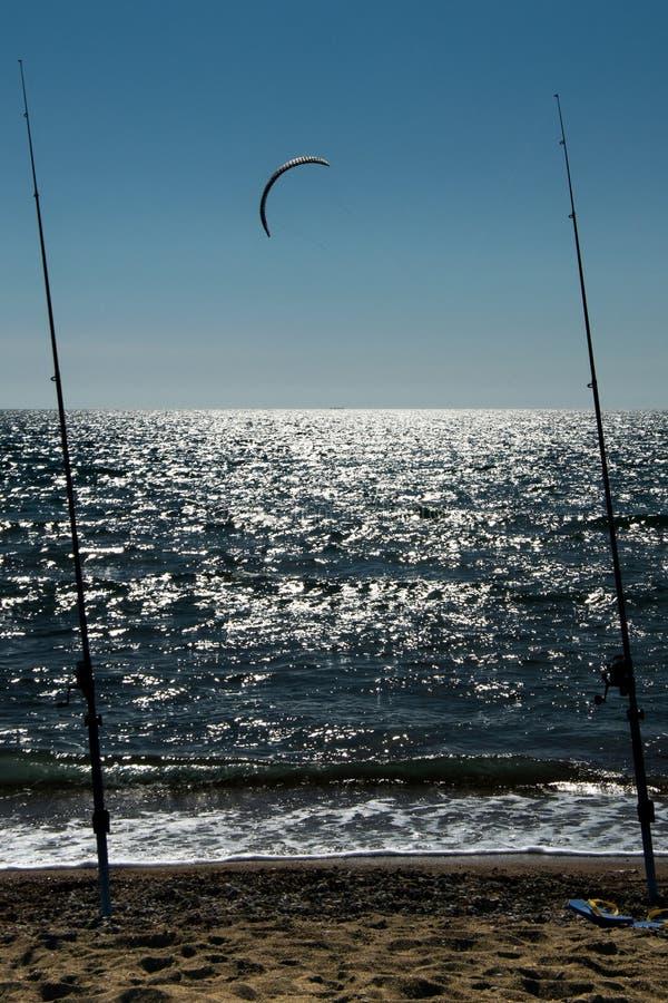 Canne da pesca sui precedenti del mare con kitesurfing immagini stock libere da diritti