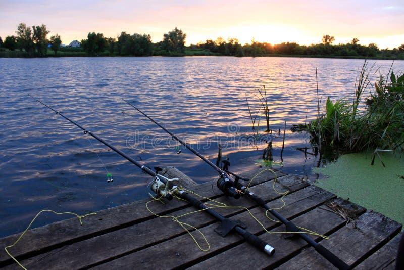 Canne da pesca sul ponte di legno al tramonto immagini stock