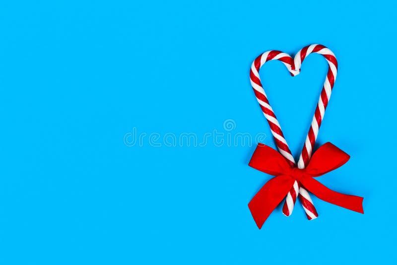 Canne de sucrerie de vue supérieure barrée dans des couleurs de Noël dans la forme d'un coeur avec l'arc rouge sur le fond bleu c photos stock