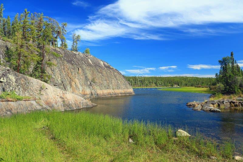 Canne ed Outcroppings canadesi del granito dello schermo lungo Cameron River, parco territoriale nascosto del lago, Territori del immagini stock