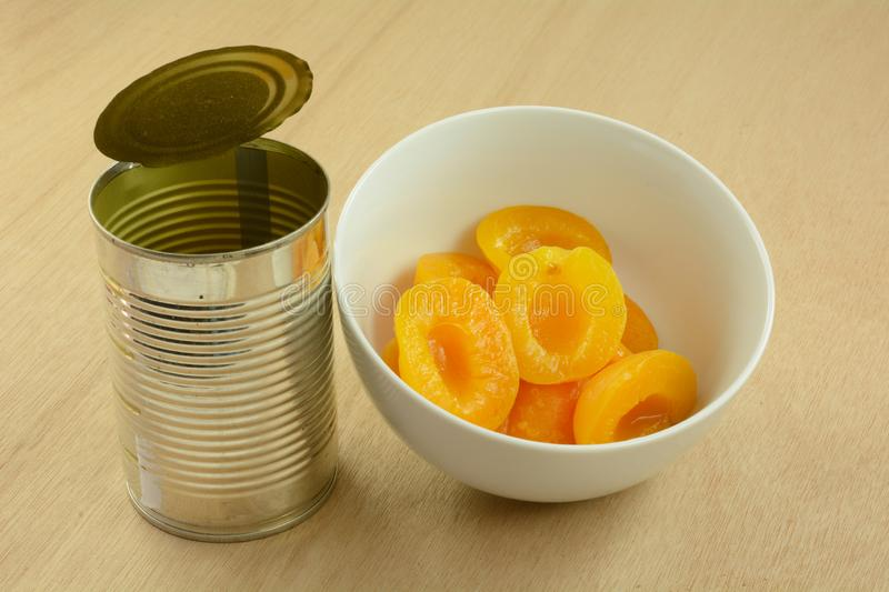 Canned apricot halves. In white bowl next to opened can on wooden table stock photography