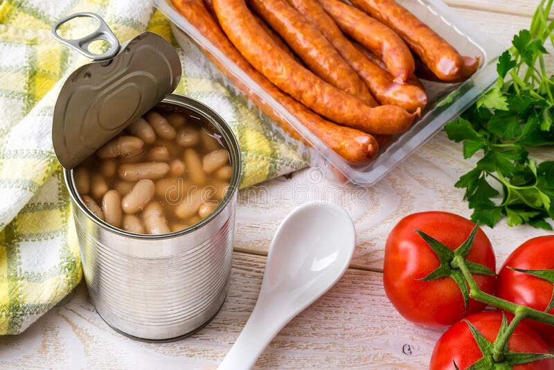 Canned backed beans in an open tin can with pull tab near thin sausages, tomatoes and ceramic spoon on a wood table. Bean is. Source of vegetable protein and royalty free stock images