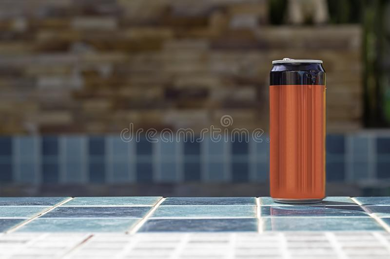 Canned drink red and black on the tiled floor beside the pool stock photos