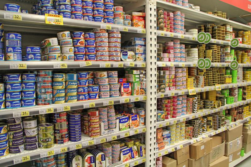 Canned fish on shelves of supermarket store royalty free stock photo