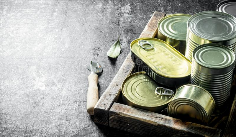 Canned food in tin cans on a wooden tray. On dark rustic background royalty free stock photo