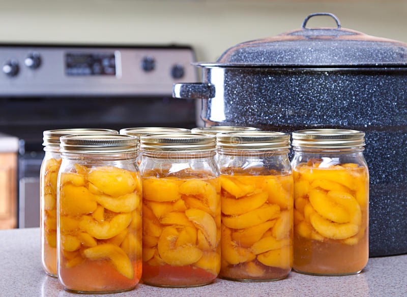 Canned peaches with large pot or canner. In a kitchen stock photos