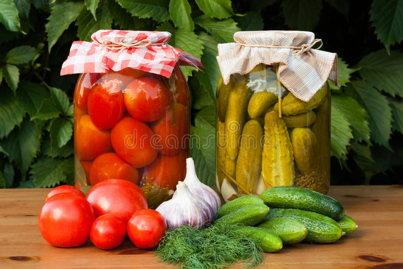 Canned Tomatoes And Pickled Cucumbers. Canned And Fresh Vegetables. Canned Tomatoes And Pickled Cucumbers In Glass Jars On Wooden Table Outdoor. Homemade Canned royalty free stock images