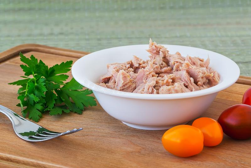 Canned tuna fillet in white porcelain bowl on a brown wooden cutting board with some cherry tomatoes, parsley and fork. Seafood, stock photography