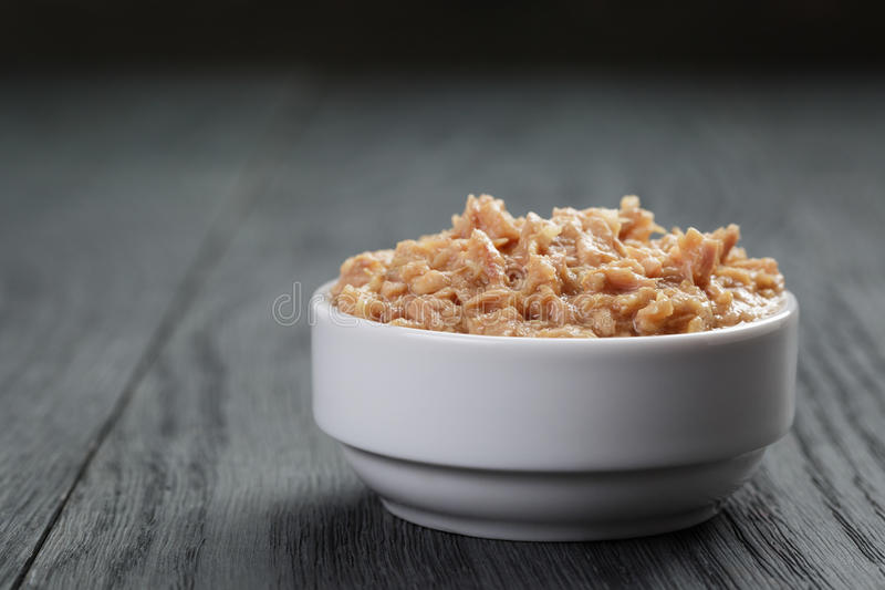 Canned tuna in white bowl on wood table stock photography