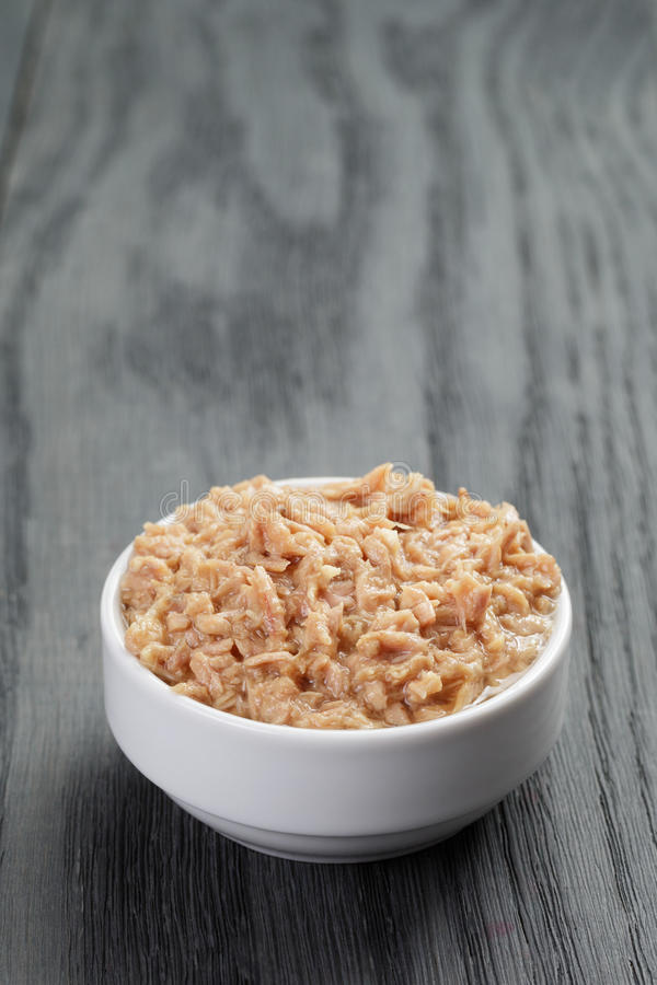 Canned tuna in white bowl on wood table royalty free stock photos