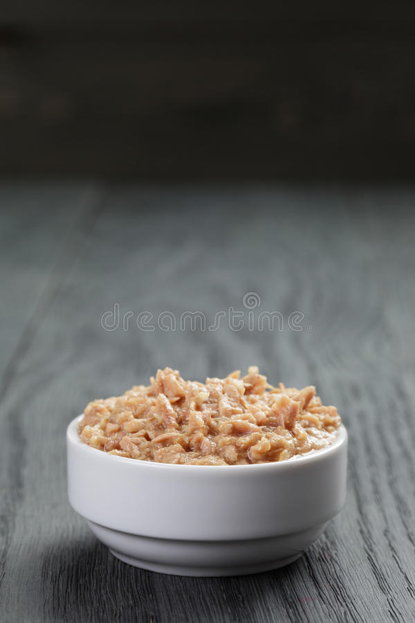 Canned tuna in white bowl on wood table royalty free stock photo