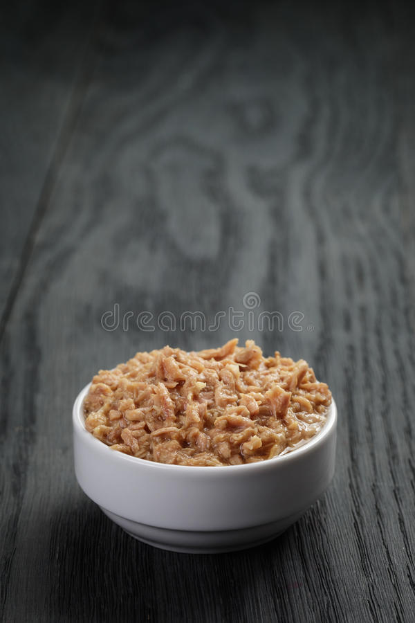 Canned tuna in white bowl on wood table stock images