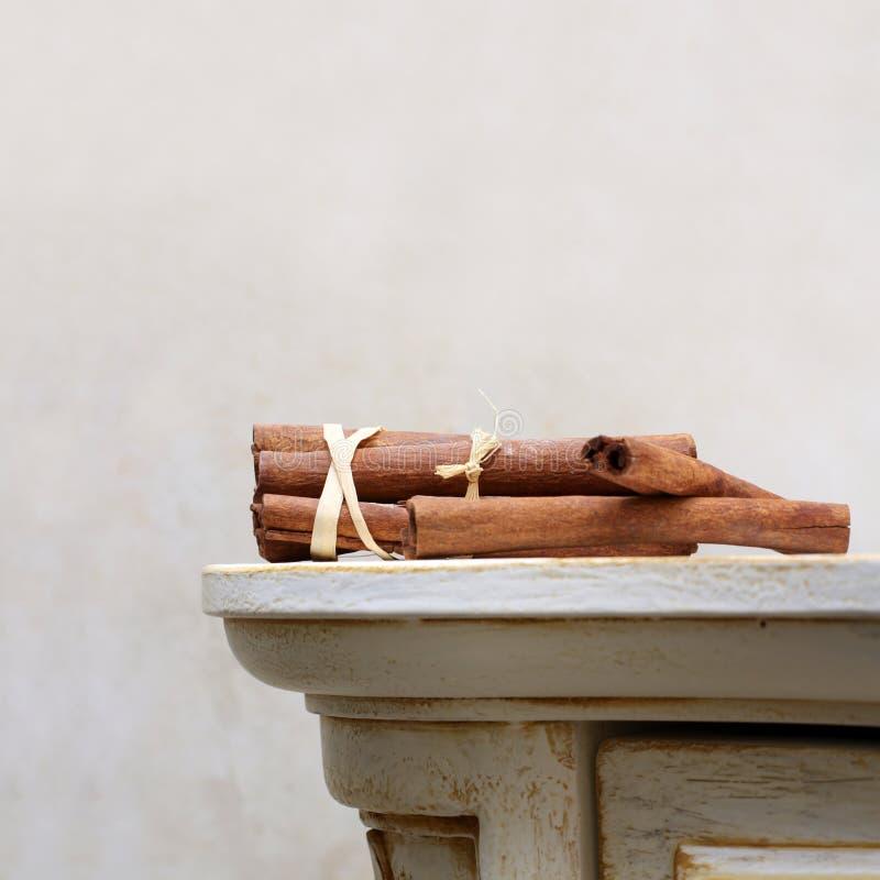 Cannella sullo scrittorio di legno dell'annata fotografie stock