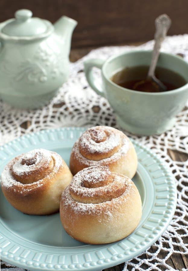Cannelle faite maison douce fraîche Rolls et tasse de thé photographie stock