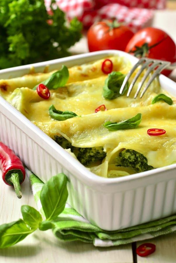 Cannelloni - испеченные макаронные изделия заполненные с шпинатом, цыпленком и сыром стоковое фото