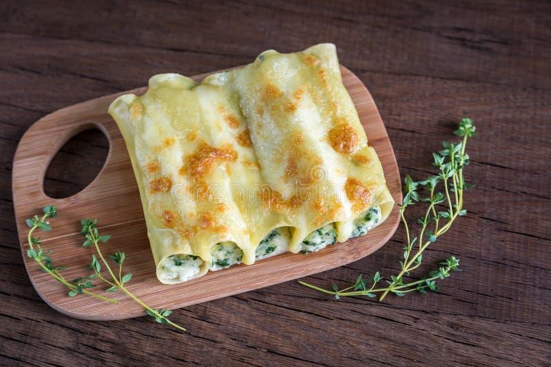 Cannelloni com ricota e espinafres na placa de madeira fotografia de stock royalty free