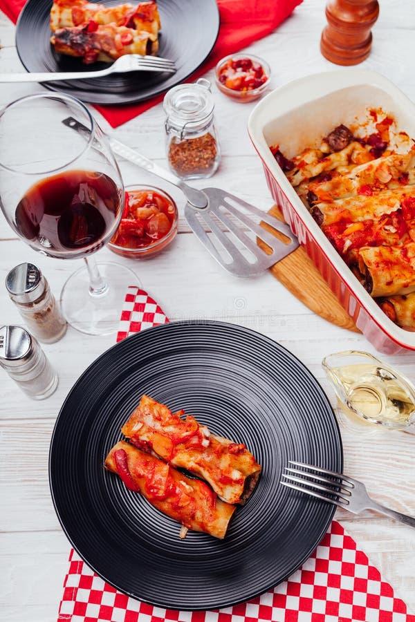 Cannelloni italiani farciti con carne tritata e serviti con salsa al pomodoro sulle bande nere Pranzo per due fotografie stock