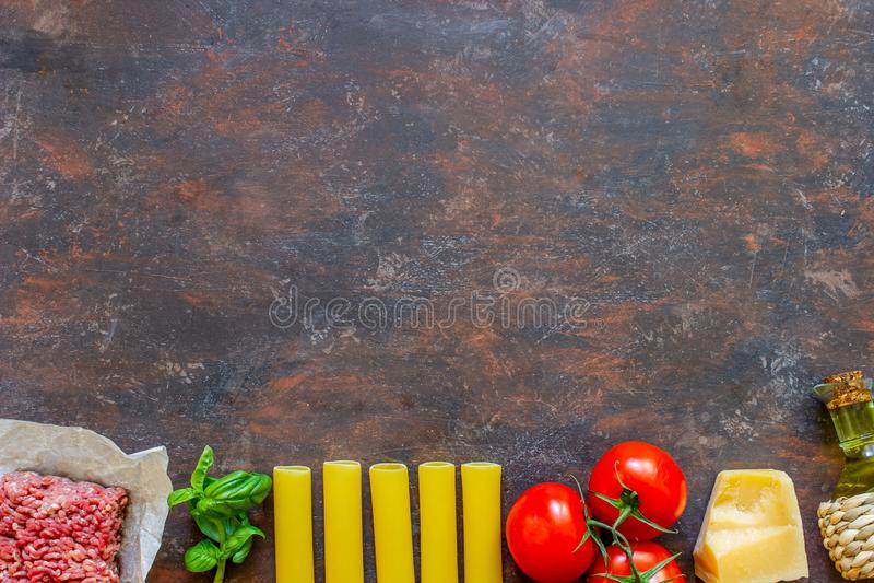 Cannelloni, pomodori, carne tritata ed altri ingredienti Fondo scuro Cucina italiana immagini stock