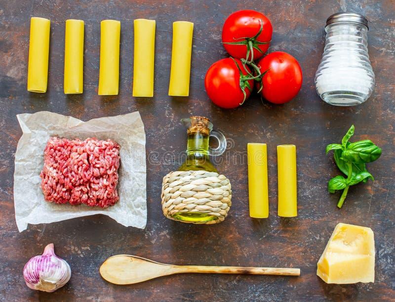 Cannelloni, Tomaten, Hackfleisch und andere Bestandteile Dunkler Hintergrund Italienische K?che lizenzfreie stockbilder