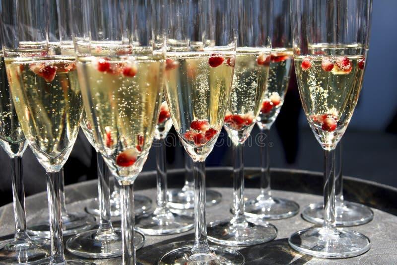 Cannelures de champagne de scintillement sur le plateau avec des graines de grenade image stock
