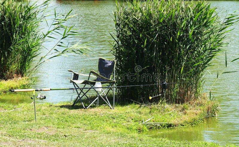 Cannes à pêche, chaise près des roseaux sur le rivage du l de pêche image libre de droits