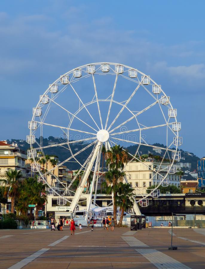 Cannes - Ferris wheel. Cannes, France - July 3, 2018: Ferris wheel installed on the Pantiero harbour area. Unidentified people walk near to wheel stock image