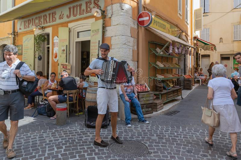 CANNES, FRANCE - August, 2018. Street musician playing on a tourist street, next to a cozy cafe with visitors royalty free stock photos