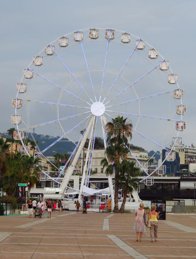 Cannes - Ferris wheel. Cannes, France - July 3, 2018: Ferris wheel installed on the Pantiero harbour area. Unidentified people walk near to wheel royalty free stock photography