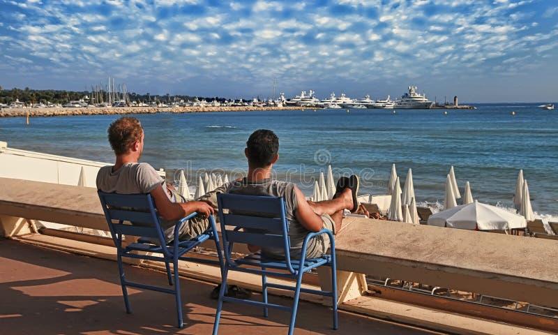 CANNES FRANKRIKE - JULI 5, 2014: Två vänner som kopplar av i stolar på Croisette promenad i Cannes, Frankrike CANNES FRANKRIKE -  royaltyfria foton