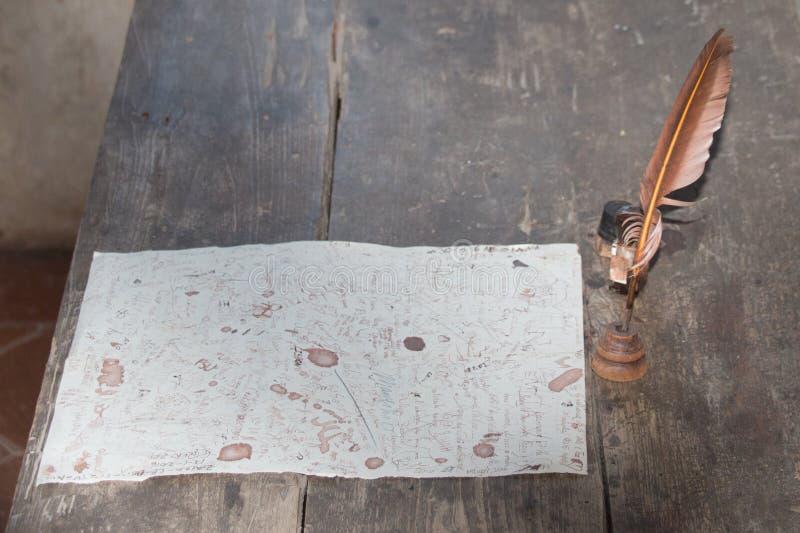 Cannette de plume et lettre non finie sur un bureau en bois photos libres de droits