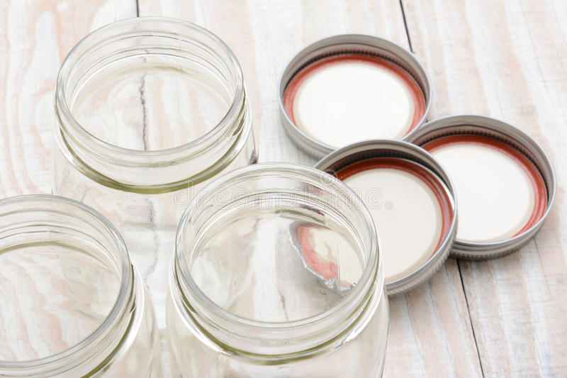Canning Jar Closeup. Closeup of three glass canning jars on a rustic wood farmhouse style kitchen table. The lids are laying in the background. Shallow depth of stock photo