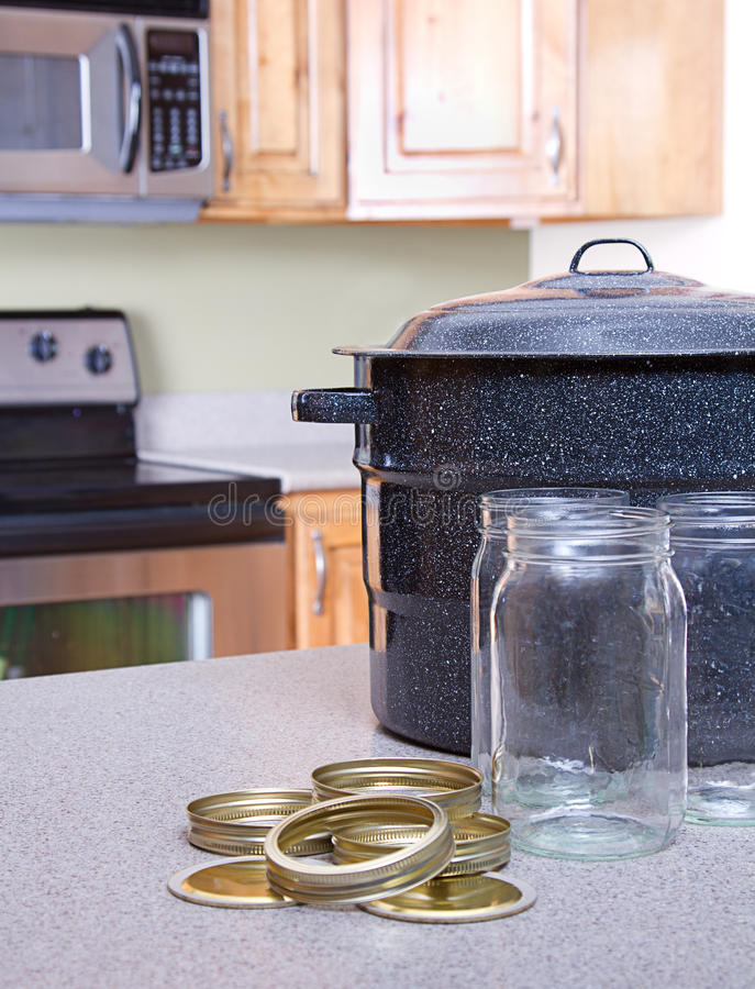 Canning jars and supplies in a kitchen. Canning jars with lids, canner or pot in a kitchen setting royalty free stock photos
