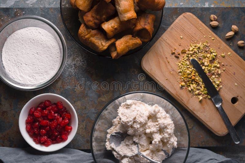 Cannoli con los ingredientes para llenar en la opinión superior del fondo de piedra fotografía de archivo libre de regalías
