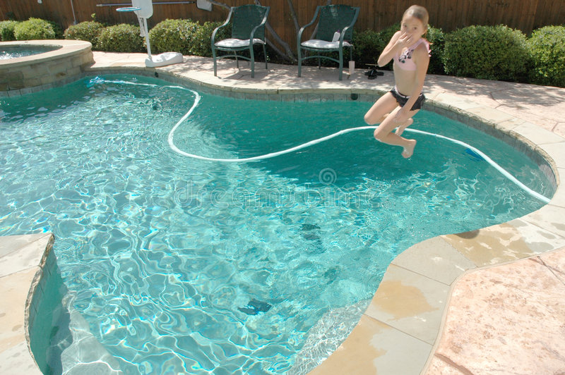 Cannon Ball. Girl runs and jumps into pool trying to do a cannon ball trick stock photos