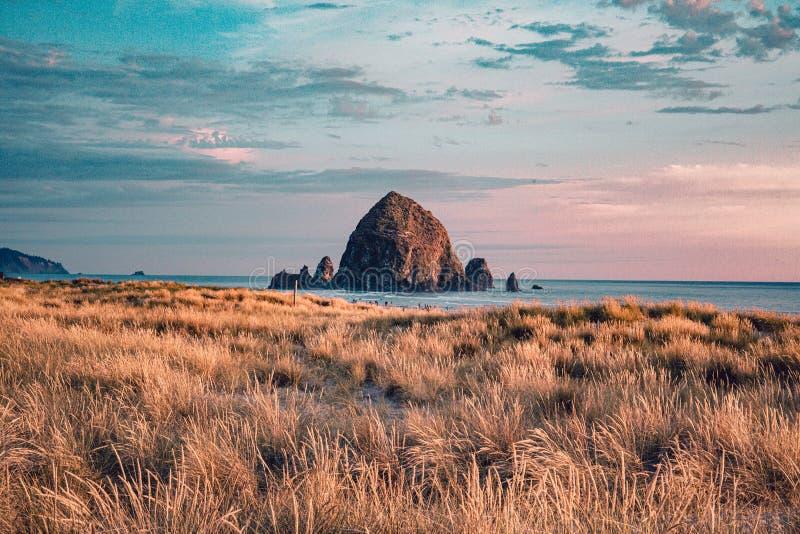Cannon Beach, costa dell'Oregon: il famoso Haystack Rock nella luce d'oro prima del tramonto immagini stock
