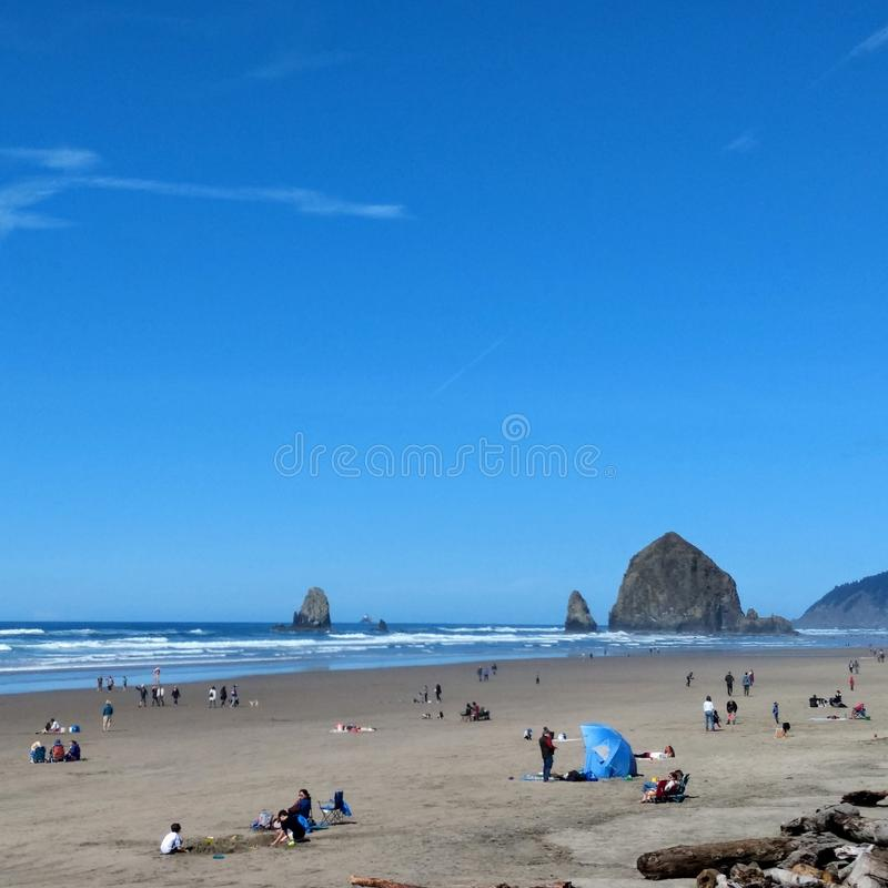 Cannon Beach, OR. Cannon beach oregon coast daytime sunny square crop haystack rock beachgoers travel toirism tourism lanscape landscape vacation spring break royalty free stock photos