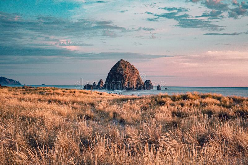 Cannon Beach, Oregon coast: the famous Haystack Rock in the golden light before sunset.  stock images