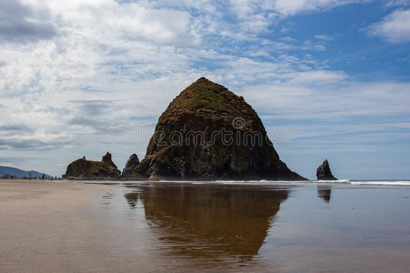 Cannon Beach, Oregon coast: the famous Haystack Rock reflects itself in the water.  stock photo