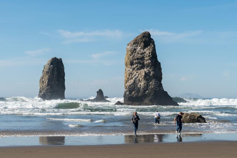 People trying to escape from the wave that just caught them in Cannon Beach, Oregon, USA. CANNON BEACH, OREGON, USA - October 17, 2018: People trying to escape royalty free stock photos