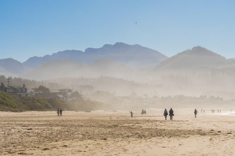 Tourists and locals enjoying the sun at Cannon beach, Oregon, USA. stock photo