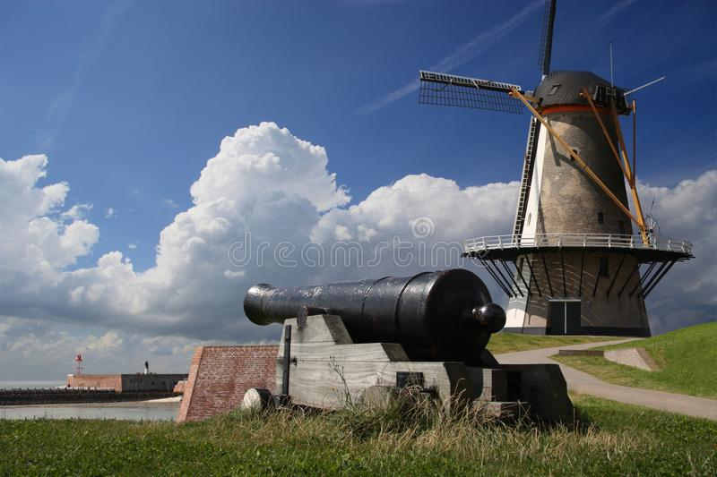 Windmill and cannon. Cannon and windmill with an old fort in the back ground on Vlissingen sea front. All modern elements were taken out of the image